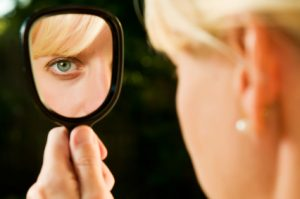 girl looking in handheld mirror,jpg