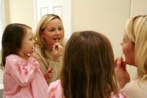 A girl puts on lipgloss with her mother